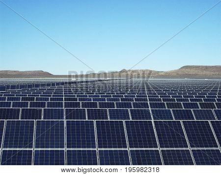 Big renewable energy farm with many solar panels with blue sky and mountains