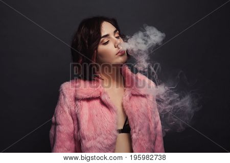 Young beautiful brunette in bra and pink fur coat breathing out smoke on dark background.