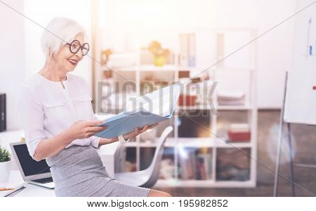 Studying the archives. Graceful mature hardworking woman sitting on the table and turning pages of the folder while working on something
