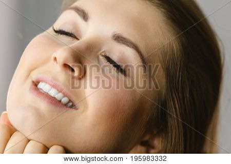 Happy attractive young woman with perfect skin complexion glowing in sunlight. Skincare concept.