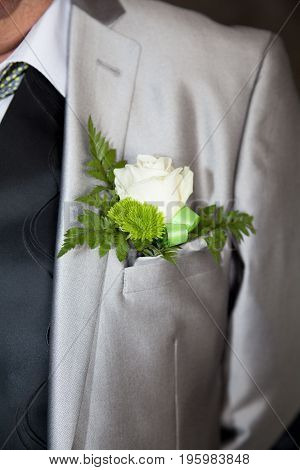 a green pinning boutonniere to groom jacket
