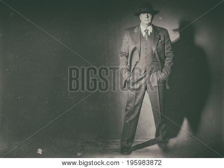 Antique Black And White Photo Of 1940 Style Gangster Standing In Front Of Gray Wall.