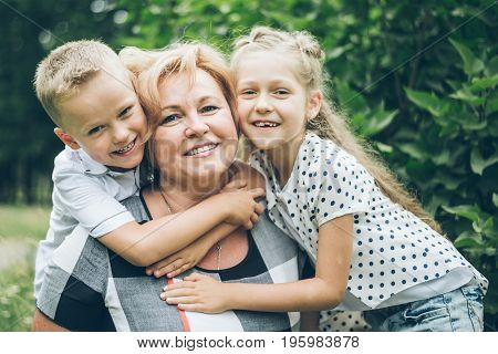 Grandmother with grandchildren hugging in the park