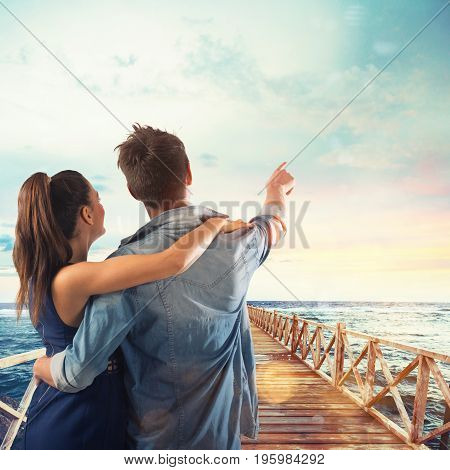 Couple of lovers points to the sky on a pier at sunset