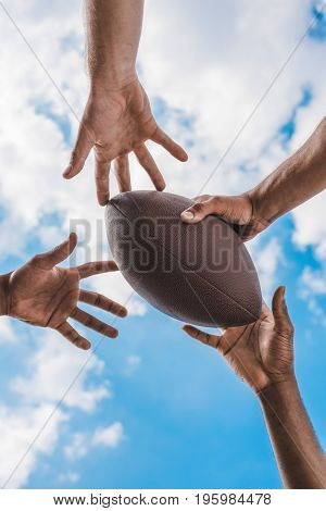 Human Hands Holding American Football Ball On Background Of Blue Sky
