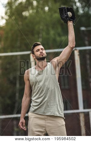 Young Handsome Man Catching Baseball Ball On Court