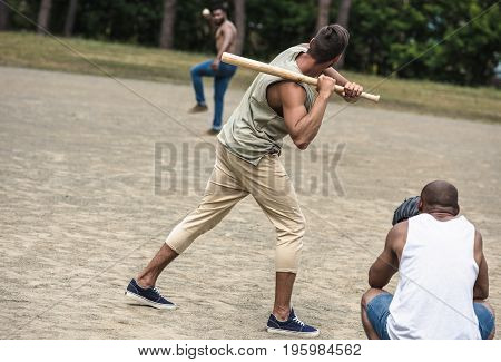 group of young multiethnic men playing baseball on court