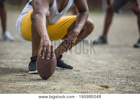Cropped Image Of Young Man Sitting With American Football Ball