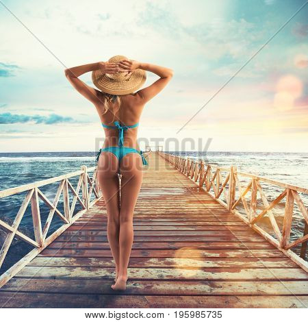 Beautiful blond girl in bikini with hat walking on a pier at sunset