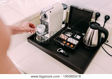 Coffee preparation concept at home by a coffee machine. Close-up image of a man's hands preparing espresso at morning.