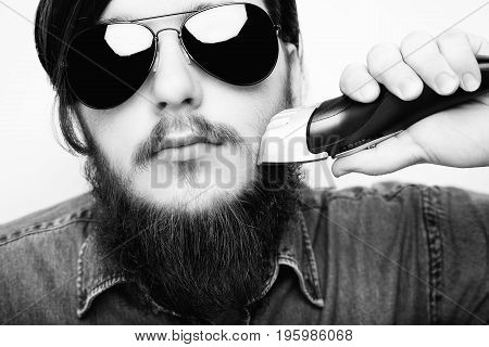 Young Hipster Man Shaving Ginger Beard With Electric Shaver Machine.