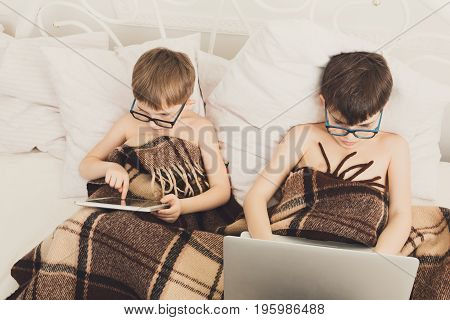 Boys in parents' bed at morning with laptop and tablet. Brothers play computer games. Siblings and gadgets. Children in glasses.