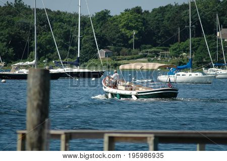 Bristol Rhode Island USA - July 24 2005: Tender heads out into Bristol harbor on summer morning