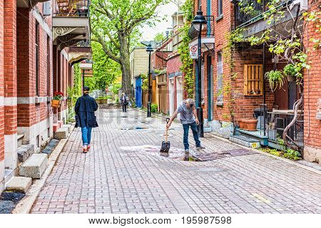 Montreal, Canada - May 26, 2017: Man Cleaning Puddle In Plateau Distric Alley In City In Quebec Regi
