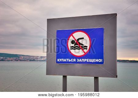 No swimming square sign against sea beach. Russian translation: No Swimming