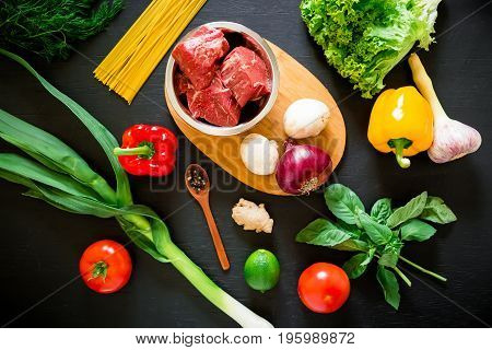 Raw meat in a metal plate on wood board, pasta and fresh vegetables on dark background. Top view. Flat lay. Food background