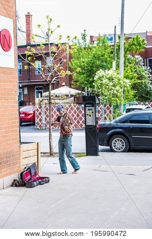 Montreal, Canada - May 27, 2017: Man Playing Violin On Street Outside Jean Talon Market Entrance In
