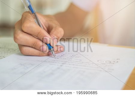 Blurred of Asian boy students hand holding pen writing fill in Exams paper sheet or test paper on wood desk table with student uniform in exam class room education concept Thailand