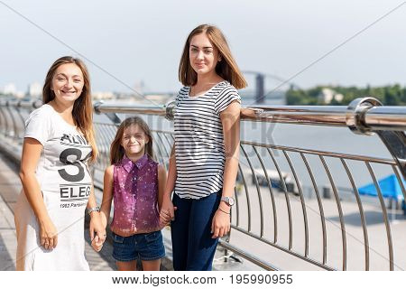 Samesex lesbian family with child on a walk in the park near the river. Lesbians mothers with adopted child, happy family, pregnant couple with kid