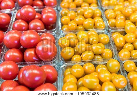 Closeup Of Red Ripe And Yellow Grape Tomatoes In Baskets At Farmers Market
