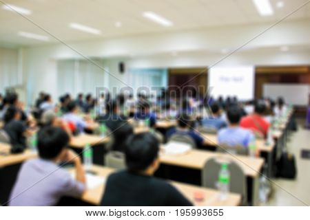 Blurred image of people during seminar in the room background.