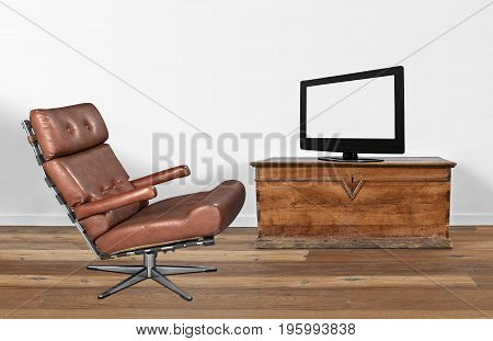 Soft brown leather vintage and stylish chair with television on old chest
