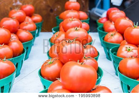 Closeup Of Red Ripe Tomatoes With Green Stems In Baskets In Farmers Market