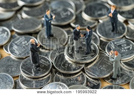 Miniature people: small figure businessmen handshaking and others clapping on stack of coin as money and financial agreement concept.