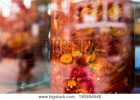 Marinated Red And Yellow Peppers In Large Jars On Display Behind Glass Window