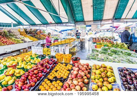 Montreal Canada - May 27 2017: People buying produce by fruit and vegetable stands at Jean-Talon farmers market with displays