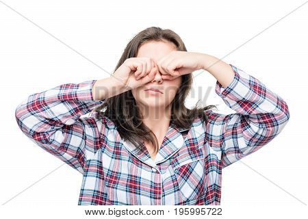Sleeping Woman In Pajamas Rubbing His Eyes With His Hands On A White Background