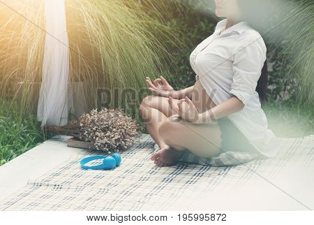 Asian pregnant woman practicing yoga at outdoor park. Female is meditating. Copy space.
