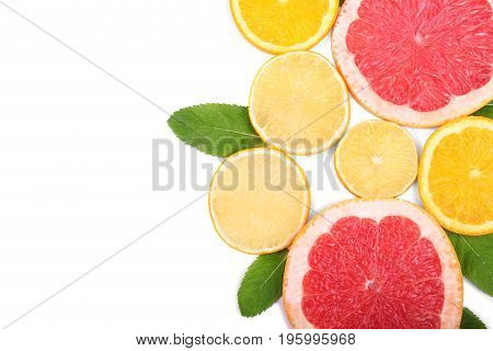A composition of juicy, fresh and ripe citrus fruits, isolated on a white background. Fresh slices of exotic and sour lemons, sweet oranges and juicy grapefruits with green leaves of mint, top view.