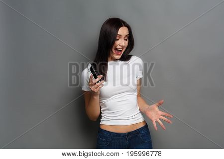 Young angry agressive woman shouting with phone, gray studio background. Furious girl wants to break mobile phone