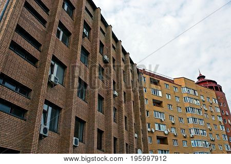 City street with brown apartment buildings, balconies and windows
