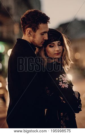Stylish Gypsy Couple In Love Hugging In Evening City Street Car Lights. Woman And Man Embracing, Rom