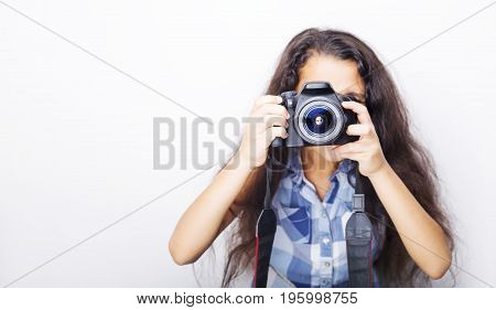 Cute brunette little girl holding an photo camera isolated on white background
