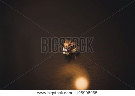 Two wedding rings on dark background. Love concept.