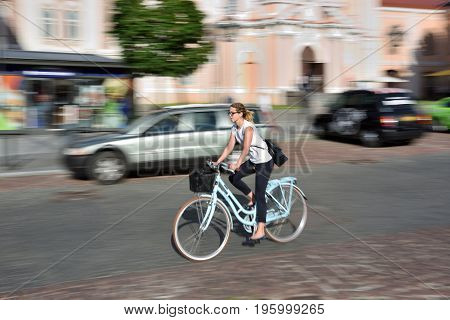 VILNIUS LITHUANIA - JULY 18: Unidentified woman ride the bicycle in Vilnius old town on July 18 2017. Vilnius is the capital of Lithuania and its largest city.