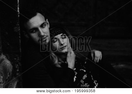 Stylish Gypsy Couple In Love Embracing In Evening City Street At Old Building. Woman And Man Hugging