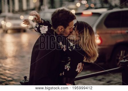 Stylish Gypsy Couple In Love Kissing In Evening City Street At Moving Car Lights. Woman And Man Embr