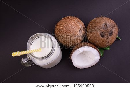 Top view of ripe, fresh, appetizing whole and cut coconuts and mason jar with coconut milk on a dark purple background. A straight and long yellow straw in the transparent mason jar.