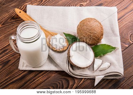 Exotic coconut milk in a mason jar, juicy cocos, green leaves and brown wooden spoon with coco chips on gray cloth and on a dark wooden background.