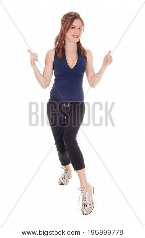 A beautiful young woman in a exercising outfit standing over white background with her thump up and smiling.