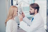 Health care medicine eye sight and technology concept. Side profile photo of brunet bearded optician checking blond`s lady patient intraocular pressure at eye clinic poster