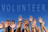 volunteer group raising hands against blue sky background poster
