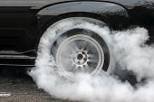 Drag racing car burns rubber off its tires in preparation for the race . poster