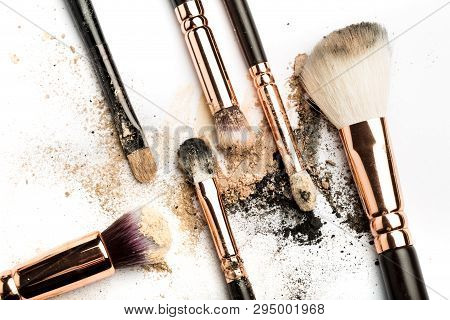Close-up side view of professional make-up brush with natural bristle and black ferrule with crashed eyeshadow isolated on white background poster