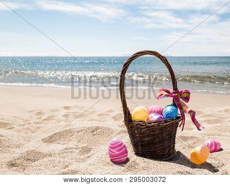 Easter Basket With Color Eggs On The Sandy Beach Near Ocean