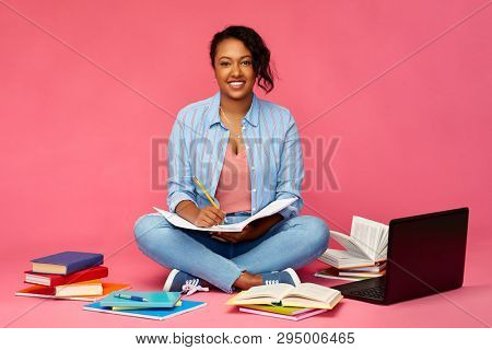 education, school and people concept - happy african american young student woman with books and laptop computer sitting on floor and writing to notebook over pink background